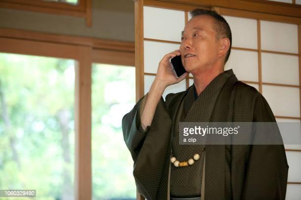 スマートフォンで電話する中高年男性 - 着物 ストックフォトと画像