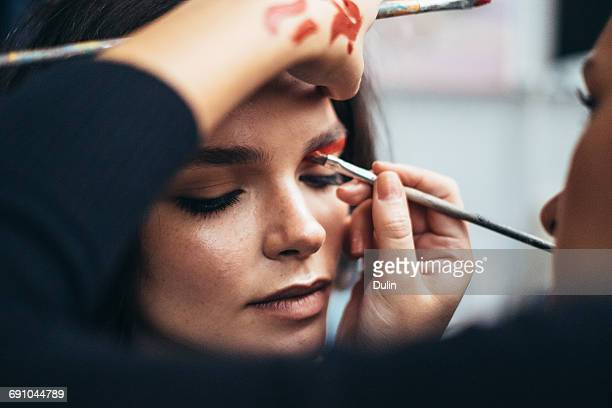 make up artist applying eye shadow to a woman - beautician stock pictures, royalty-free photos & images
