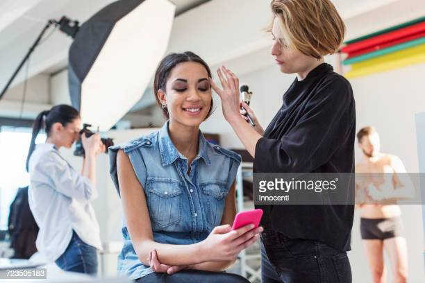 Make up artist applying eye shadow to model in photography studio