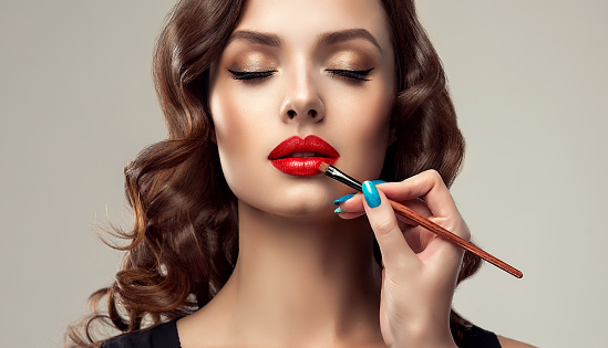Make up artist is working with face of gorgeous model. Cosmetic, manicure and make up. 924985612