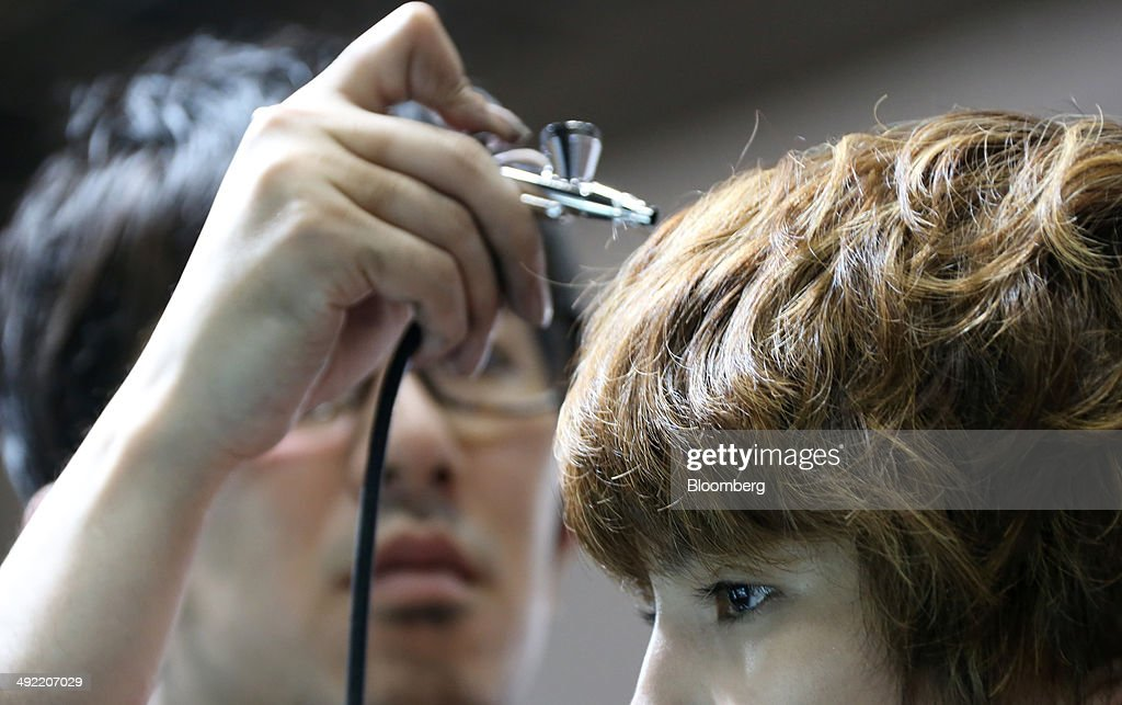 A make up artist, left, demonstrates an air blush at the Trico Industries Ltd. booth at the Beautyworld Japan fair in Tokyo, Japan, on Monday, May 19, 2014. The business-to-business trade fair hosted by Messe Frankfurt is held through May 21. Photographer: Tomohiro Ohsumi/Bloomberg via Getty Images
