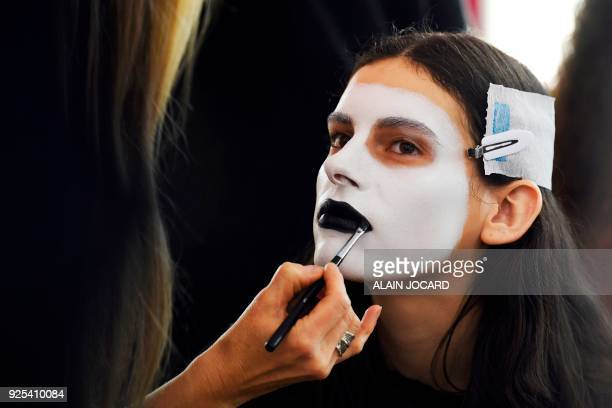 A make up artist puts makeup on a model's face in the backstage prior to the Aalto's 2018/2019 fall/winter collection fashion show on February 28...