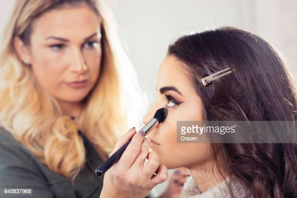 Make up artist putting professional make up on female model before going to stage
