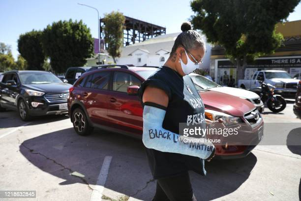 Makeda Harding waits for a procession to depart Leimert Park for downtown Los Angeles for a memorial service to honor George Floyd and demand justice...