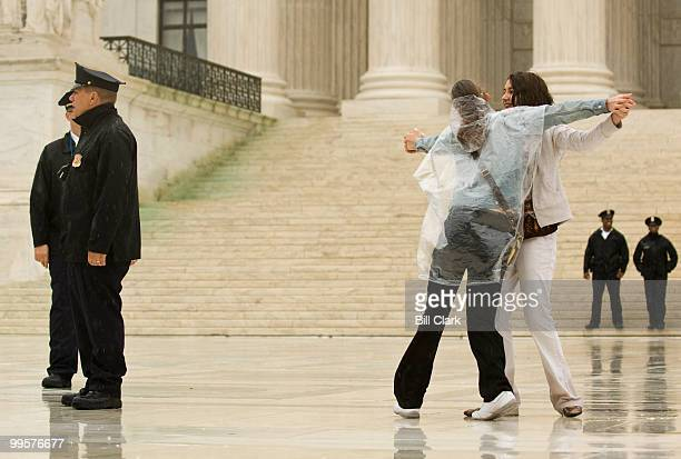 Makenzi Smith of Norman Okla and Mallee McGee of Midwest City Okla dance on the Supreme Court plaza in the rain on Wednesday April 29 with music...