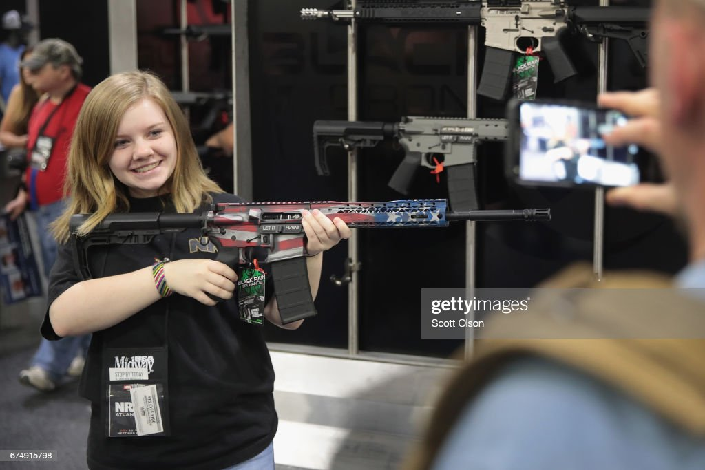 Makenzie Wynn poses for a picture for her father while holding a Black Rain Ordinance rifle at the 146th NRA Annual Meetings & Exhibits on April 29, 2017 in Atlanta, Georgia. With more than 800 exhibitors, the convention is the largest annual gathering for the NRA's more than 5 million members.