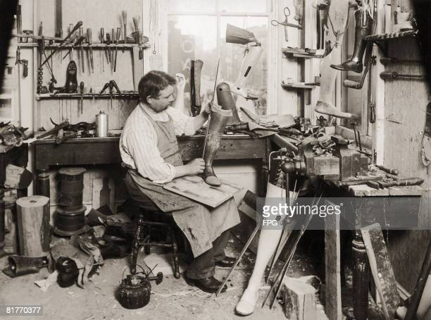 A maker of artificial limbs adjusts the braces to suit the knee joint on an artificial leg circa 1925