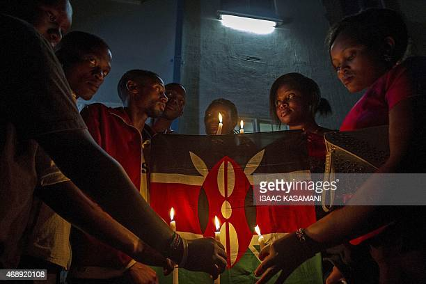Makerere University students hold candles in front of a Kenyan flag in Kampala on April 8 2015 during a candlelight vigil for the 148 people killed...