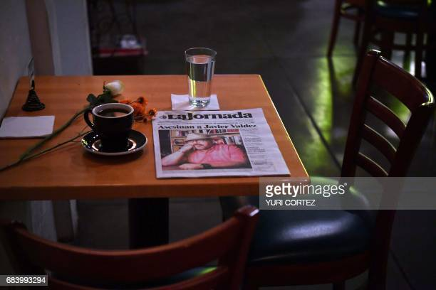 TOPSHOT A makeshift altar with a cup of coffee water glass and newspaper headlining the story of slain Mexican journalist Javier Valdez is pictured...