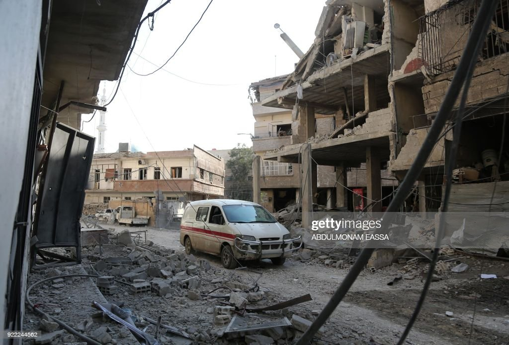 A make-shift ambulance vehicle drives through a heavily-damaged street next to a destroyed hospital that was hit by a reported regime air strike in the rebel-held enclave of Hamouria in the Eastern Ghouta near Damascus on February 21, 2018. /