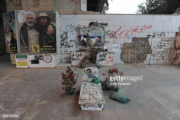 A makeshift grave and banners mark the memorial to the Islamic State massacre of 1700 Shiite Air Force cadets from Camp Speicher beneath a bridge...