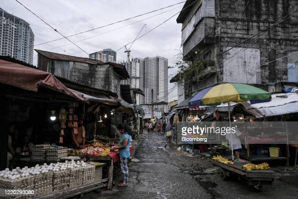 Makeshift market stands in the San Roque neighborhood as commercial high-rise buildings stand in the background in Quezon City, Metro Manila, the...