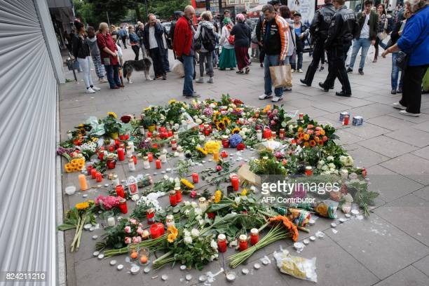 A makeshift memorial of flowers and candles is placed on July 29 2017 in front of a supermarket in Hamburg northern Germany one day after a man...