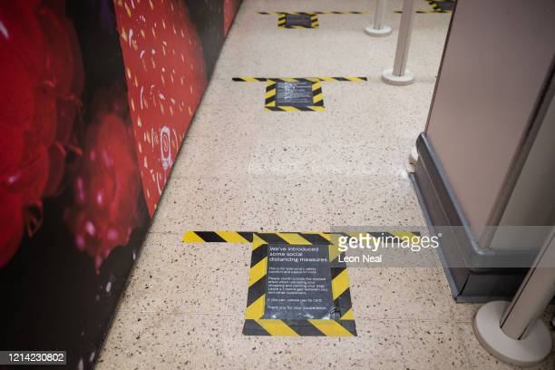 Makeshift signs on the floor of a supermarket identify how far apart customers should stand while queueing in a bid to respect the social distancing...