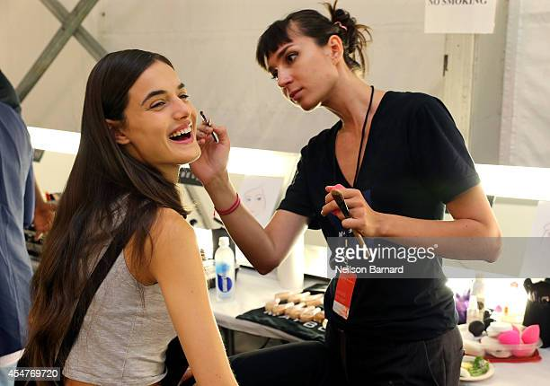 A makeup artist and a model prepare during MercedesBenz Fashion Week Spring 2015 at Lincoln Center for the Performing Arts on September 5 2014 in New...