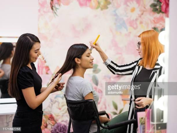 make-up artiest en medewerker werken met klant - visagist stockfoto's en -beelden