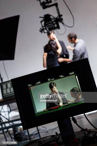 makeup artist and wardrobe stylist working on actor behind the scenes on a film set - film set stock pictures, royalty-free photos & images