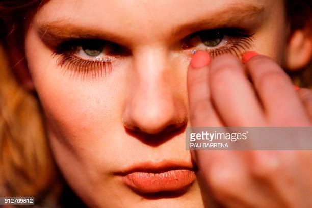 A makeup artist applies an eyelash extention on a model during the 080 Barcelona Fashion Week in Barcelona on January 31 2018 / AFP PHOTO / PAU...