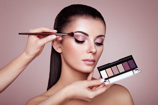 Makeup artist applies eye shadow 952087564