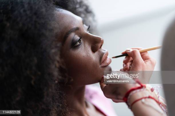 make-up kunstenaar van toepassing lipstick - visagist stockfoto's en -beelden