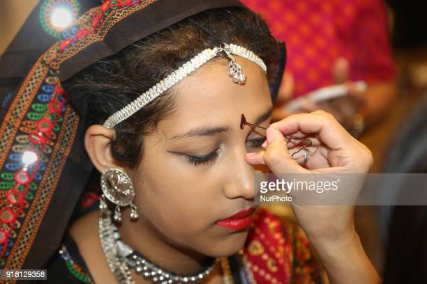 Makeup artist applies makeup to Indian girls representing the state of Rajasthan during a traditional Indian folk dance competition held in...