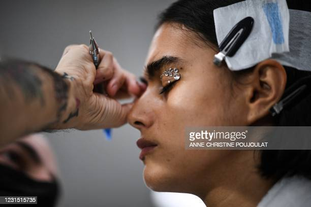 Make-up artist applies rhinestones on the eyelids of a model in the backstage prior to the Coperni AW21 Women's Fall-Winter 2020-2021 Ready-to-Wear...