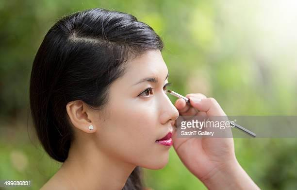 Make-up artist applying bright base eyeshadow
