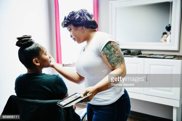 Makeup artist applying eye shadow during makeover