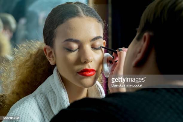 A make-up artist applying eyeliner to a model.