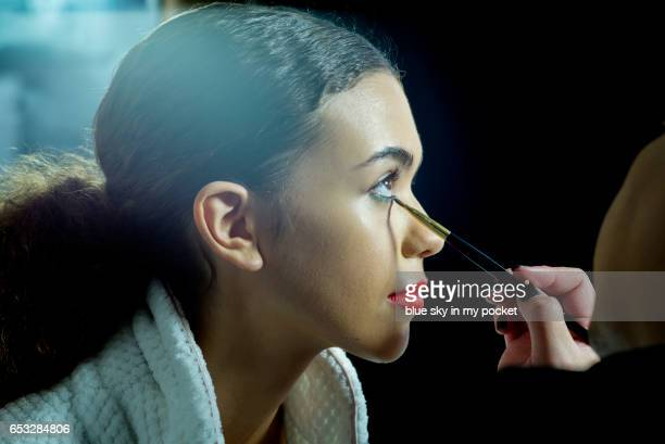a make-up artist applying eyeliner to a model. - eye liner stock pictures, royalty-free photos & images