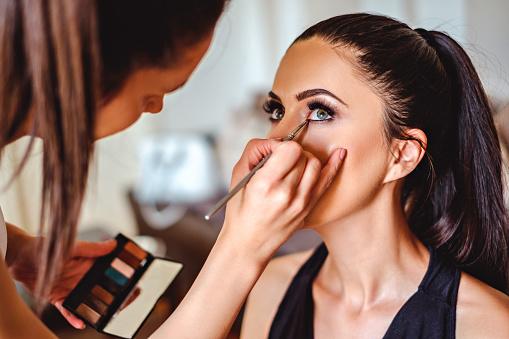 Makeup artist applying eyeshadow on a girl 687244776