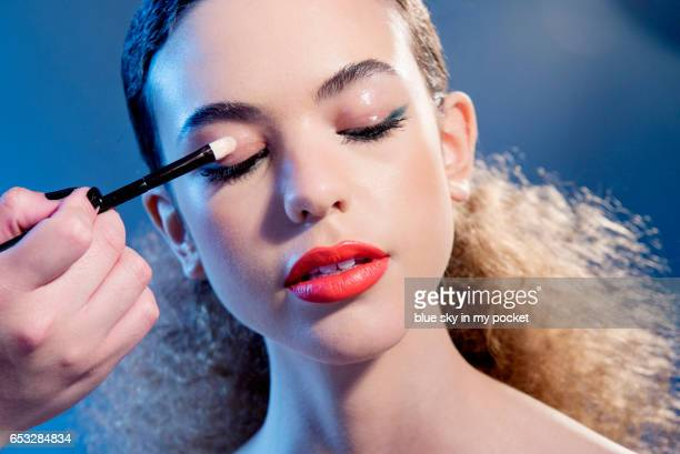A make-up artist applying glossy eight hour cream to the eyelids of a model.