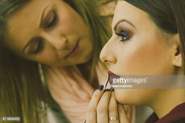 Makeup artist applying makeup on beautiful female model lips