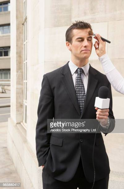 Makeup artist applying make-up to newscaster outdoors