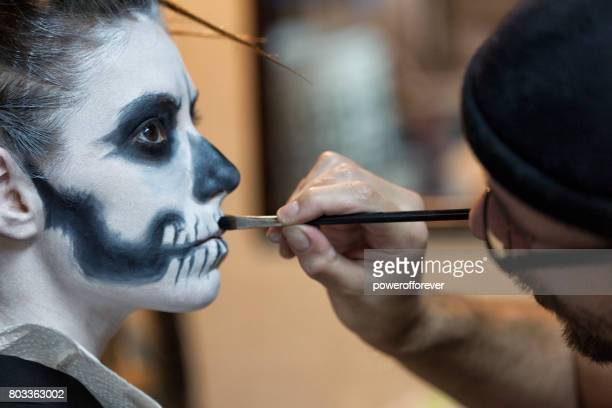 makeup artist applying skeleton makeup on a woman - stage make up stock photos and pictures