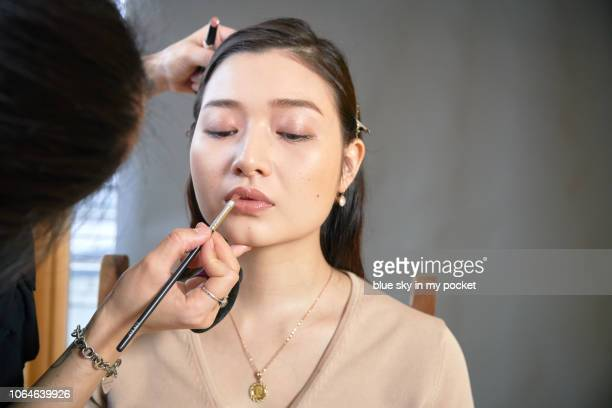 a make-up artist at work applying lipstick to a model - somente japonês - fotografias e filmes do acervo