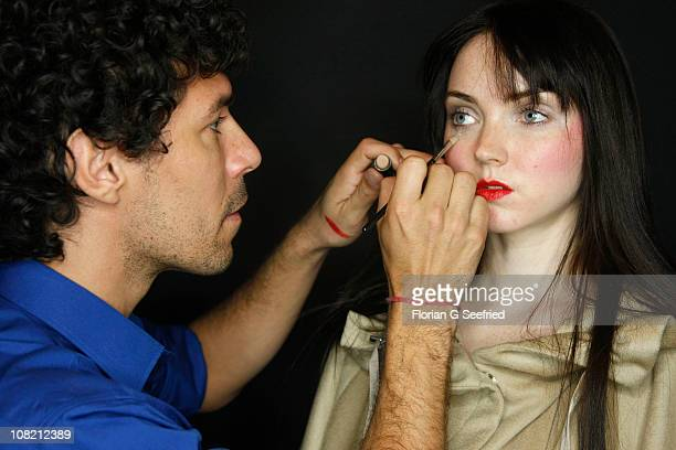 Makeup artist Boris Entrup prepares model Lily Cole backstage at the Anja Gockel Show during the Mercedes Benz Fashion Week Autumn/Winter 2011 at...