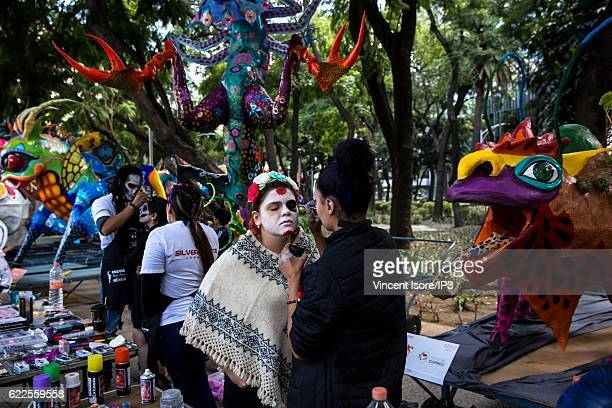 A makeup artist creates a makeup on the face of a participant to the 'Catrinas Parade' a joyful annual event celebrated at the Day of the Dead on...