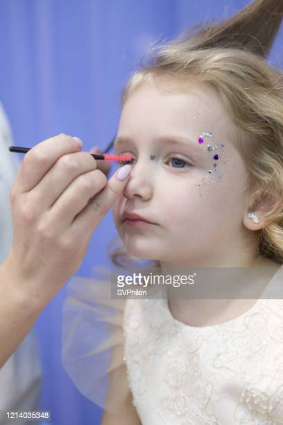 makeup artist does holiday makeup for a child. - beauty salon ukraine stock pictures, royalty-free photos & images