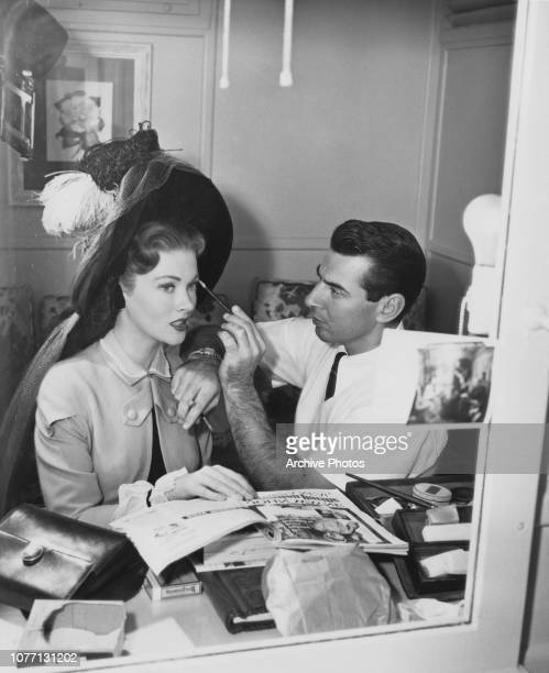 Makeup artist Eddie Polo a former silent screen actor works on American actress Paula Raymond on the set of the MGM film 'The Tall Target' 1951