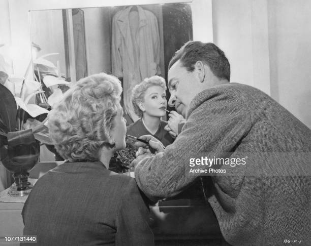 Makeup artist Jim Barker works on American actress Anne Baxter on the set of the Warner Bros film 'The Blue Gardenia' 1953