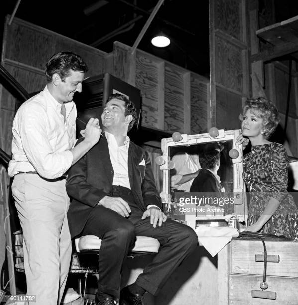 Makeup artist John Jiras is photographed behind the scenes with stars Peter Falk and Joanna Barnes on the set of the CBS television legal drama The...