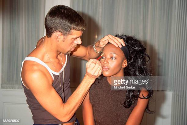 Makeup artist Kevyn Aucoin applies makeup to supermodel Naomi Campbell backstage at a Todd Oldham fall line fashion show