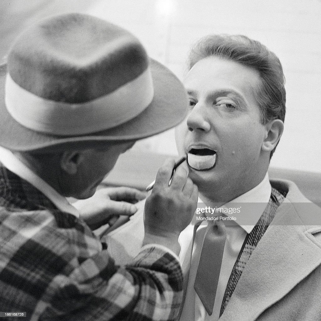 A make-up artist makes up the famous tv presenter Mike