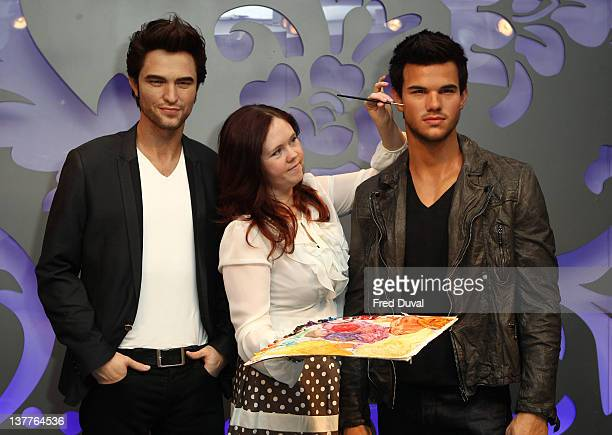 Makeup artist Maria Callinan putts the final touches to the Madame Tussauds' latest wax figure of Taylor Lautner beside the wax figure of his...