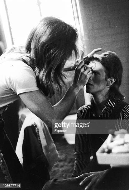 Makeup artist Pierre La Roche prepares English singer David Bowie for a performance as Aladdin Sane 1973