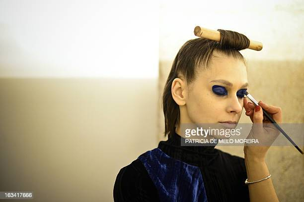 A makeup artist prepares a model before Portuguese designer Alexandra Moura's Autumn/Winter 20132014 collection show during the 40th edition of the...