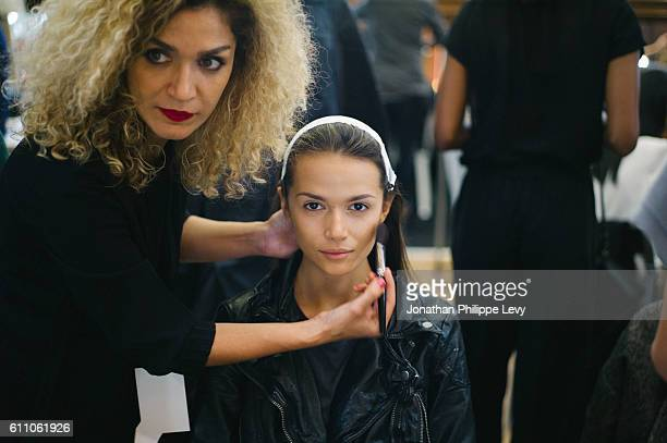 A makeup artist prepares a model prior to the Fashion Farm Foundation show as part of the Paris Fashion Week Womenswear Spring/Summer 2017 on...