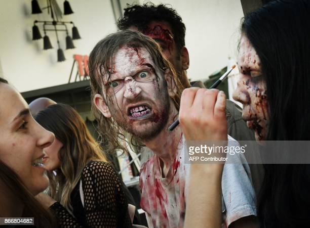 Makeup artist prepares PETA supporters as zombies during a Halloween themed protest against consumption of animal meat in Hollywood, California, on...