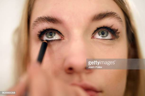 A makeup artist prepares the models ahead of the Irene Luft show during the MBFW January 2018 at ewerk on January 17 2018 in Berlin Germany